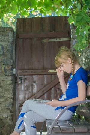 wicket gate: young teenage girl sit on bench at backyard under the thickets of grapes and reed journal book with amazed expression oh her face. Stock Photo