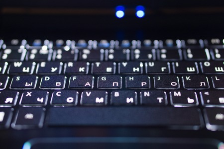 closeup of black notebook laptop keyboard with english and russian illuminated letters symbols buttons. macro low key shot