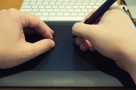 scribe: Mans hands with pen who working on professional graphic tablet