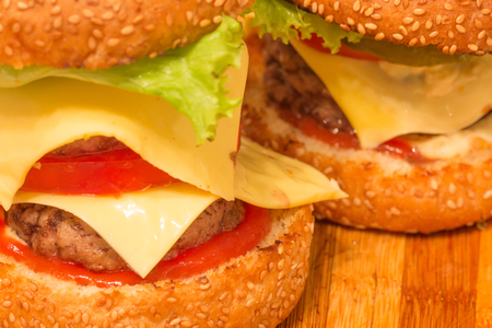 two homemade burgers with beef cutlet, cucumber, lettuce, onion and yellow cheese with olive on top. on wooden cutting board. closeup shot with negative space Stock Photo