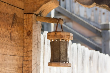 wooden lantern on ancient house made from tree board in ethnic style in the medieval settlement