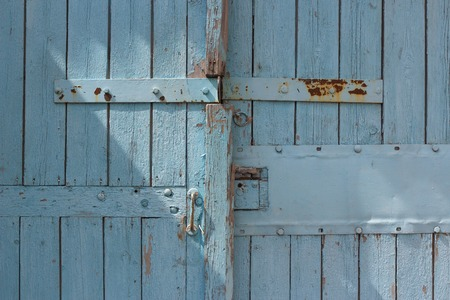access point: old light blue retro vintage wooden gates to garage with peeled painting with strips from rusty metal