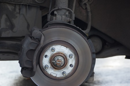 Car without wheel waiting for tyre wheel replacement at service, road assistance Banco de Imagens