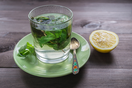 warming therapy: a cup of fresh mint tea on a dark wooden table with leaves of fresh mint and lemon. top angle view Stock Photo