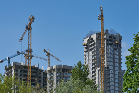 unfinished building: cityscape development of a new modern houses in urban city blue sky and trees around