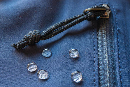large rain drops dew on dark waterproof weatherproof membrane clothes. closeup macro shot of buckle, zipper, sealed pocket, fastener 免版税图像