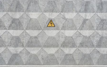 Mur de béton gris avec panneau d'avertissement de danger électrique. triangle jaune avec le tonnerre Banque d'images - 81280481