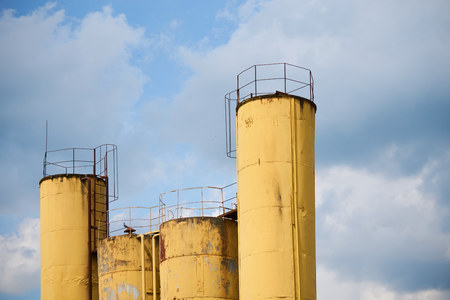 vivid yellow storage pipes of the abandoned factory against the blue sky