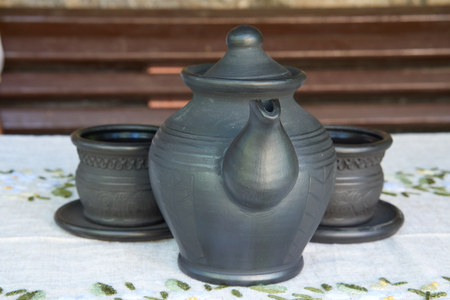 brave ceramic tea kettle with two shy cups behind on a table