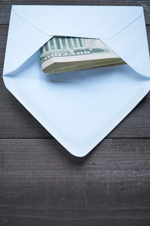 money packs: white mailing envelope with the pack US Dollars cash inside on a dark wooden table Stock Photo