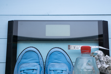 blue sneakers, bottle of clear water and measuring tape lay on a digital scale. top view from above aerial view. simple neat and clean concept for those who want to loose weight