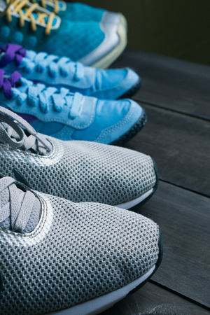 three pairs of run sneakers in a row on dark background. family goes to gym, do fitness prefer active healthy lifestyle