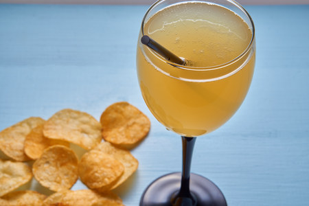 closeup of golden mixed drink shake with straw and blurred potato crisps on background. focus on glass with drink