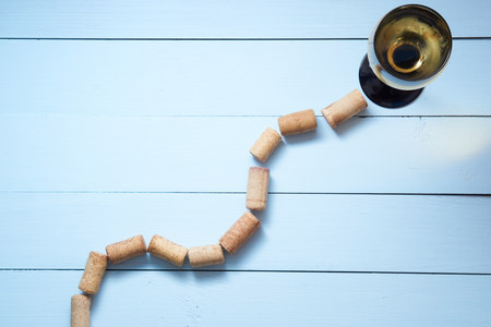 way path to wine glass with white wine made with corks. aerial top shot with copy space on blue wooden background