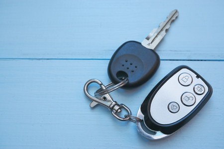 car keys with security alarm on blue desk. top view with lot of copy space