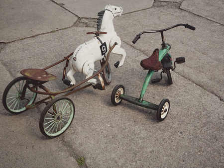 vintage bicycle tricycle toys with white horse on a playground Standard-Bild