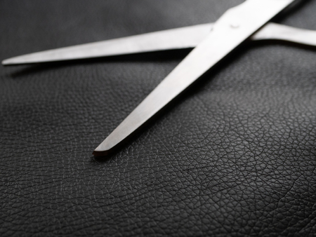 shiny metal scissors on a piece of natural black leather. craft work small business concept. selective focus on leather