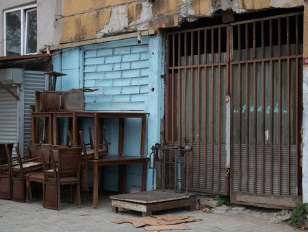 closed iron gates of small warehouse at the local market with large vintage industrial scales, empty chairs, tables