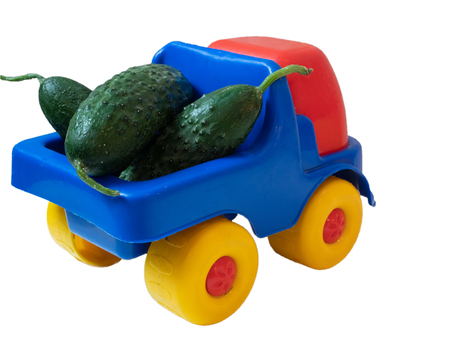 colorful vivid toy car truck with fresh green cucumbers. closeup from behind back part shot cutout isolated on white background