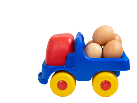 little toy truck full of fresh organic farm yellow eggs. vegetarian food market delivery service concept. side closeup shot cutout isolated on white background