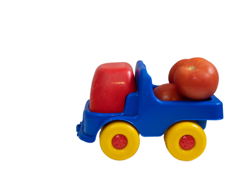 colorful vivid toy car truck with red tomatoes. side shot cutout isolated on white background