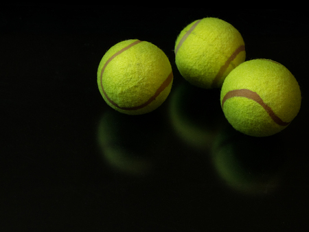 tree sport vivid yellow tennis balls on glossy dark black background. for gold, silver and bronze finals. low key closeup shot 写真素材