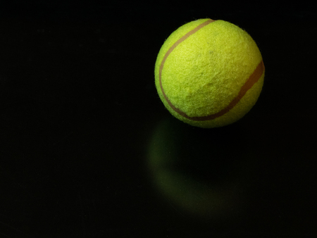one yellow green tennis ball on dark glossy surface background. first place gold winner at Wimbledon Championship concept