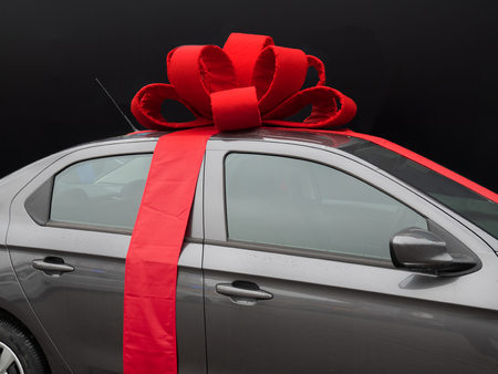 gray car with red ribbon on dark black background. perfect gift present