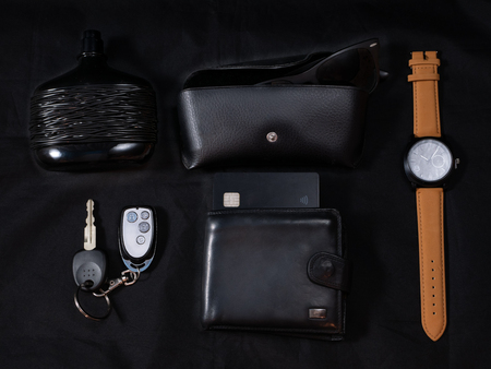 man every day carry set edc to go on dark black background - parfume, shades, glasses, wrist smart watches, car keys, purse with credit card. low key close-up flat lay shot made from the top