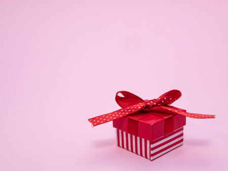 small red gift cardbox with ribbon and bow on pink background with copy space 写真素材