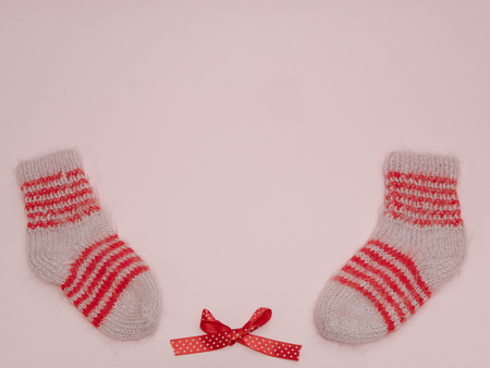 pair of handmade woolen socks and red bow on pink background