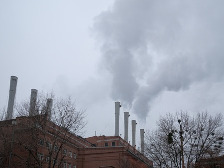 wide photo of factory plant pipe chimneys with smoke in air. smog is all around city, global pollution concept which cause medical problems like cancer carcinoma Standard-Bild - 115076588