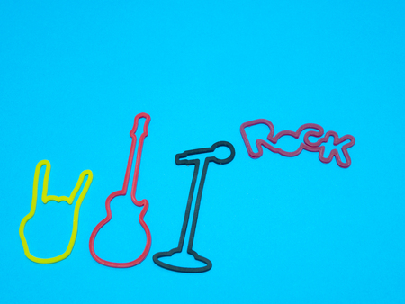 rock concert banner ticket concept on blue background - guitar, microphone, rock word out of mic and devils horn