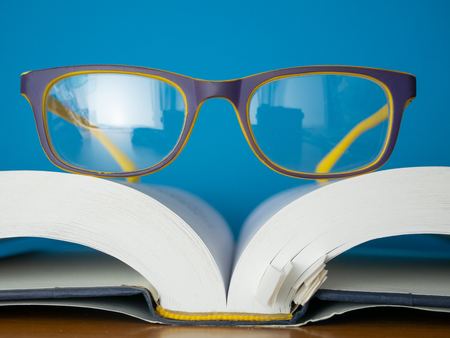 macro photo of reading glasses lay on top of opened book. education and learing concept