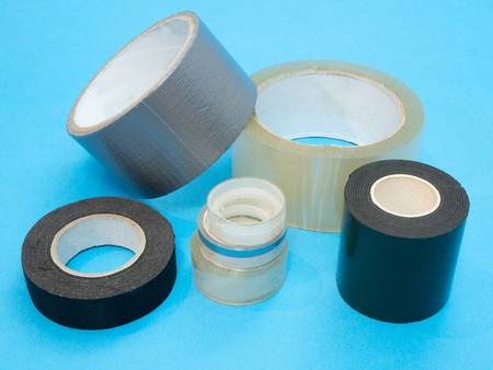 heap pile of rolls packing sticky duct tape various size and different purpose on blue background Stock Photo