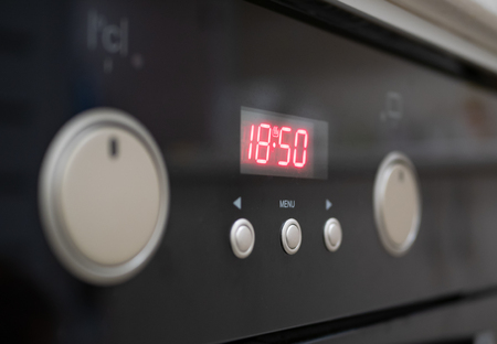 closeup of control buttons and time display of modern kitchen electrical oven. selective focus on red numbers of digital clock. control dials hidden