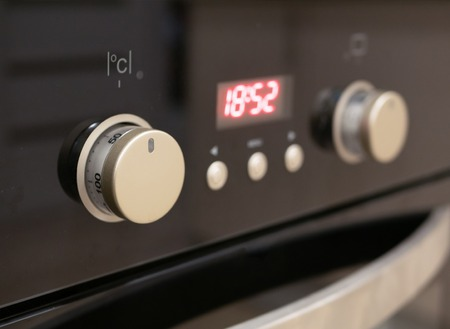 closeup of control dials and buttons of modern kitchen oven. selective focus on closest knob with blurred digital display