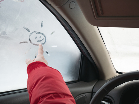 girls hand draw sun on frozen car window at winter Stock Photo