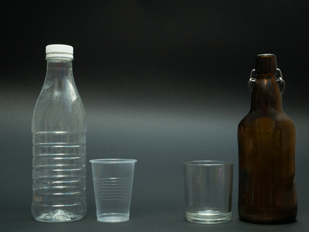 plastic vs glass materials bottle and cup on black dark background