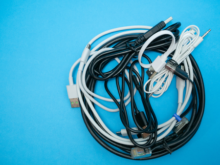 bunch heap of different cables and wires on blue background. flat lay image