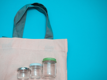 few empty glass jars on fabric bag ascending sizes. popularity growth of natural materials for retail stores