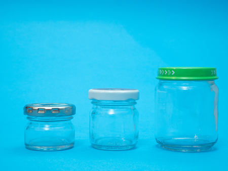 closeup of three glass jars on blue background. different sizes and unlabeled