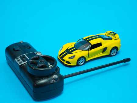 small race sport rc toy radio controlled with Remote Control. auto in yellow with black stripes on blue background