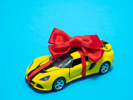 close-up small yellow toy car with red ribbon and bow on blue background as gift present 写真素材