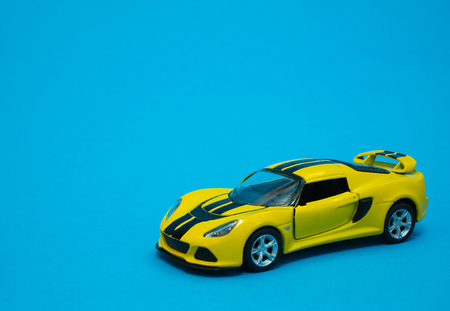 closeup of yellow toy sport car on blue background 写真素材