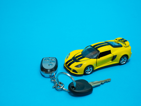 closeup of yellow toy sport car and keys on blue background