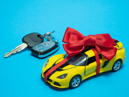 small yellow toy car with red bow on blue. auto keys blurred on background
