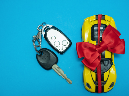 small toy yellow sport car with bow and keys on blue background. view from top. flat lay 写真素材