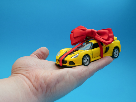 little yellow toy car with red bow on hand as gift present
