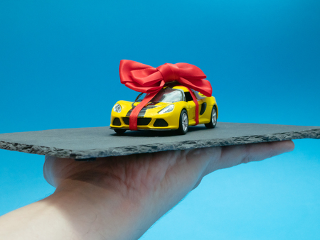 mans hand with small toy car with red bow on black rock plate as a daily dish